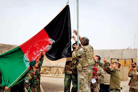 5月2日,阿富汗士兵与美军士兵在赫尔曼德省一处军事基地升起阿富汗国旗。当日,美军向阿富汗国民军移交该处军事基地。图/新华