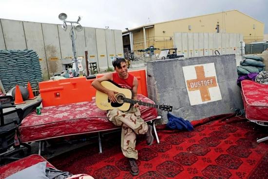 7月5日,阿富汗帕尔万省,美国和北约军队已从巴格拉姆空军基地全部撤离。一名阿富汗士兵弹奏着美军留下的吉他。