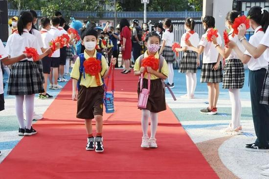 2021年9月1日,北京小学通州分校两名一年级新生戴着大红花走进校园。/视觉中国