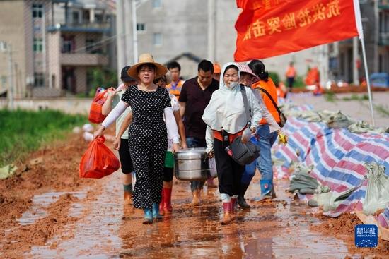 """在江西省鄱阳县鄱阳镇江家岭村,由平均年龄超过五十岁的阿姨们组成的抗洪""""阿姨团""""给武警战士送来绿豆汤(2020年7月11日摄)。新华社记者 周密 摄"""