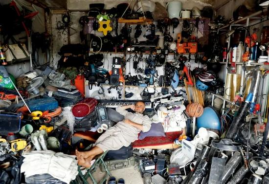 7月5日,巴格拉姆空军基地外,一名阿富汗男子在他的商店里休息。他的商店主要出售美国二手物资。本版图/澎湃影像
