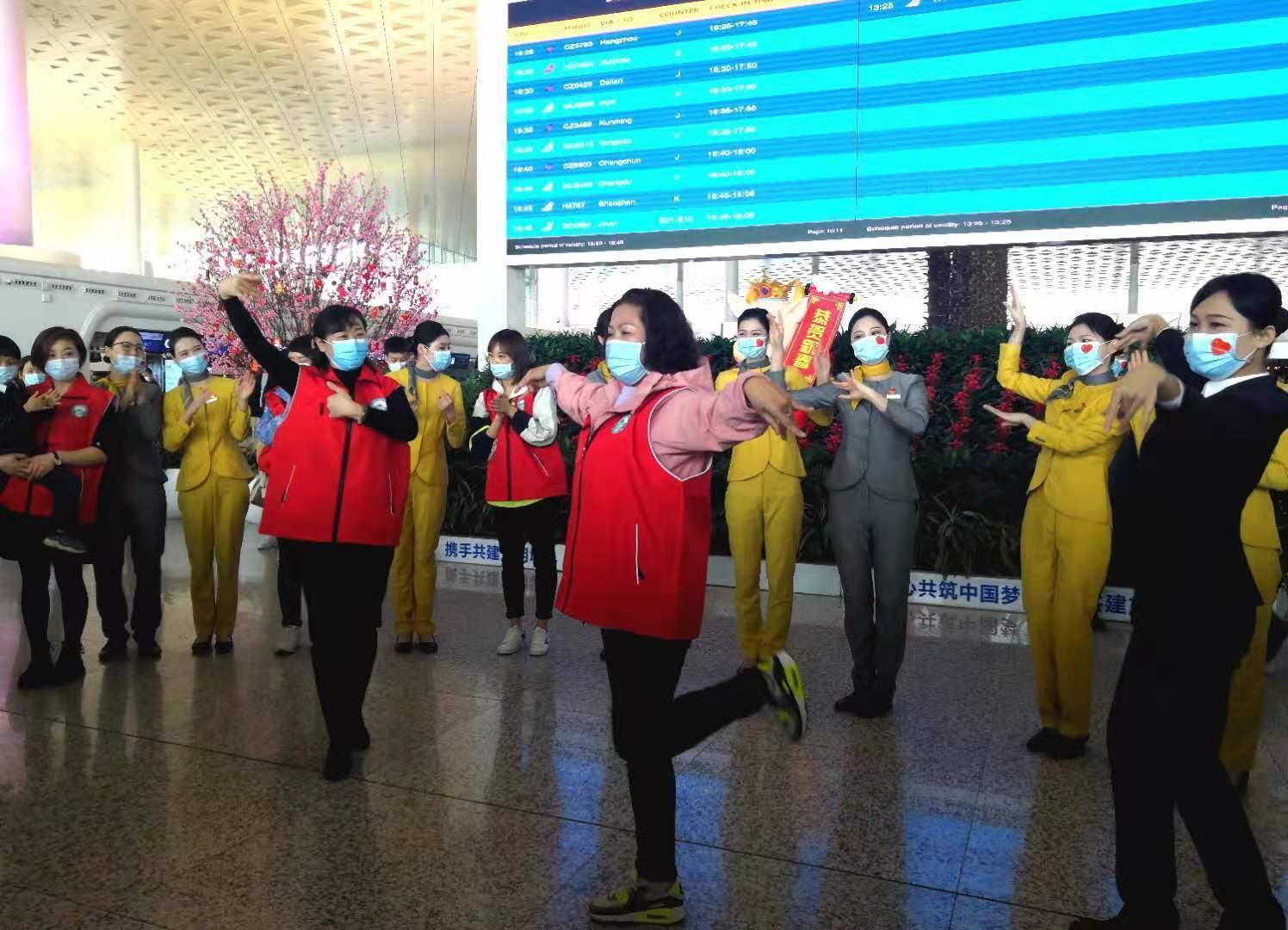 (机场工作人员与新疆援鄂医疗队员一起跳新疆舞。王郭骥摄。)