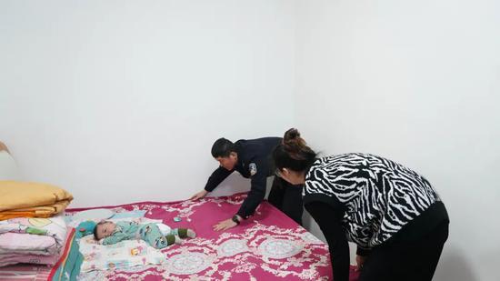 ▲3月6日,警务室里,史先强和沈欣在哄四个月大的儿子浩浩睡觉。新京报记者解蕾摄