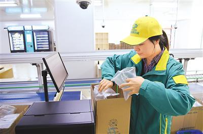 """重庆市中医院""""聪敏药房""""做事人员在对煎煮好的中药进走装箱。新华社记者 王全超摄"""