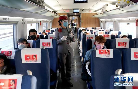 2月22日,乘务员在G3105次专列上向返岗务工人员讲解防疫注意事项。当日,来自河南安阳、新乡、周口、平顶山等地的700多名务工人员搭乘G3105次定制专列去往浙江杭州返岗复工。新华社记者 李安 摄