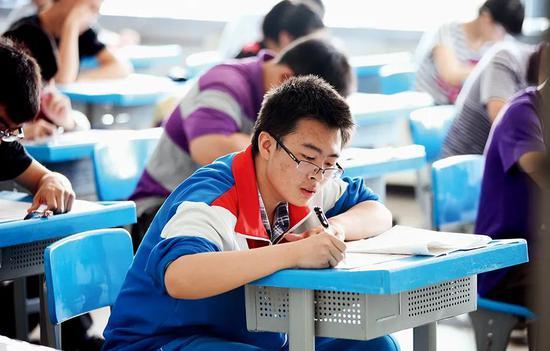 高考考场上考生作答语文试卷。图/中新