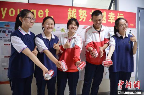 """6月23日,高三年级学生拿着印有""""祝金榜题名""""的定制饮品放松游戏。 刘文华 摄"""