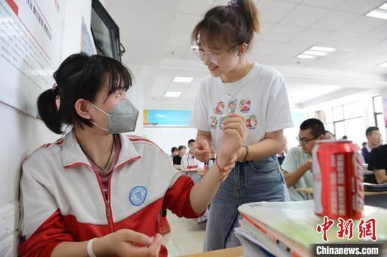 6月23日,老师为一名高三年级学生戴上端午五色绳。 刘文华 摄