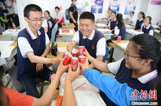 """6月23日,高三年级学生互相碰杯,定制的饮品印有""""祝金榜题名""""。 刘文华 摄"""