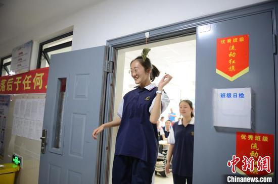 """6月23日,一名高三年级学生经过教室门口时,跳起顶到粽子,希望高考高""""粽""""。 刘文华 摄"""