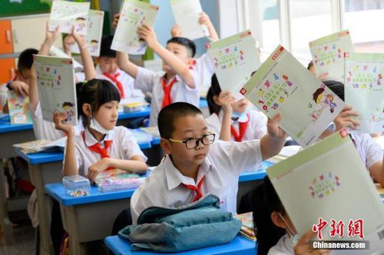 资料图:小学生在教室内领取新书。中新社记者 韦亮 图