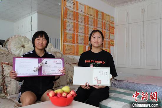 图为姜博双(左)、姜敬双手捧录取通知书。 胡建华 摄