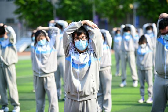 4月27日,北京高三复课首日,北京科大附中。下午课后半小时户外运动,学生们也全程佩戴口罩。视觉中国供图