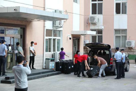 工作人员将装有考卷的拉杠箱搬入车的后备箱。新京报记者 王飞 摄