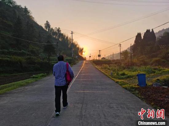 王金良又一次背上书包,走上前往孩子家中的路。 叶路顺 摄