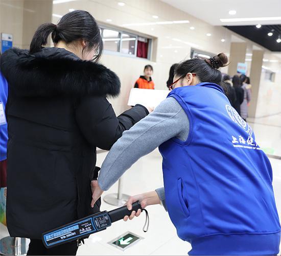 上海健康醫學院春招校測平穩有序,考務人員正細致地對考生進行安檢。何思哲 圖