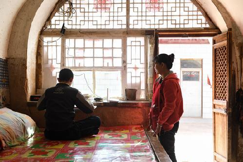 3月10日,刘进才的母亲李玉连(右)在一旁观看孩子上网课。