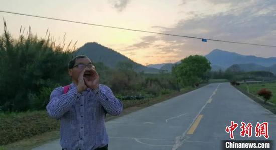 清晨,王金良在路边呼喊学生领作业。 叶路顺 摄