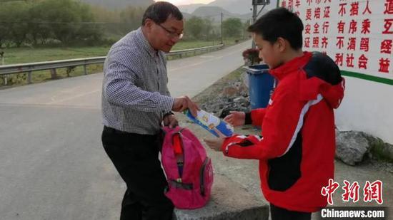 王金良背着书包,给学生发前一天批改的作业。 叶路顺 摄