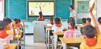 """图为新圩学校龙家坊教学点,老师用""""班班通""""给学生上课。 杨雄春摄"""