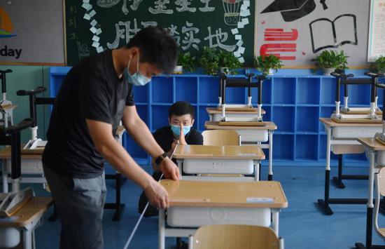 8月24日,188比分\北京教育学院附属丰台实验学校,教师根据地面的标识码放桌椅。