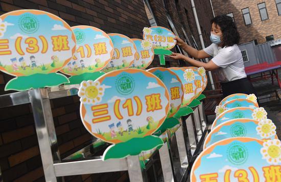 8月24日,188比分\北京教育学院附属丰台实验学校,一名教师在摆放学生错峰放学标牌。
