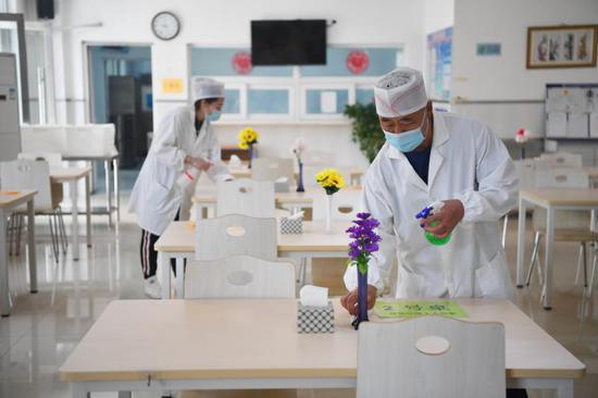 8月24日,188比分\北京教育学院附属丰台实验学校,食堂工作人员在对饭桌进行消毒。