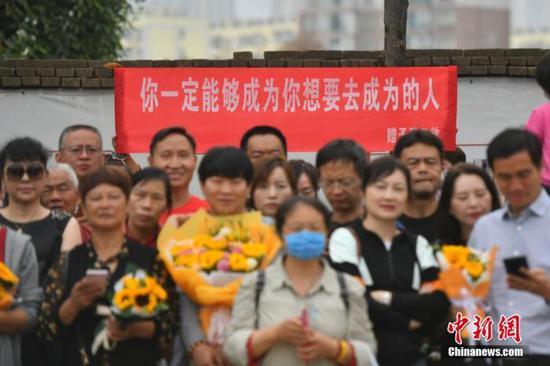 资料图:6月8日,云南省昆明市的考生结束2021年全国高考。图为考试结束后,一幅助考标语前有考生和家长合影留念。 中新社记者 刘冉阳 摄