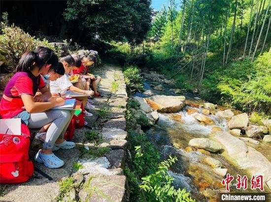 图为孩子们在山间溪水旁写生作画。李明明摄