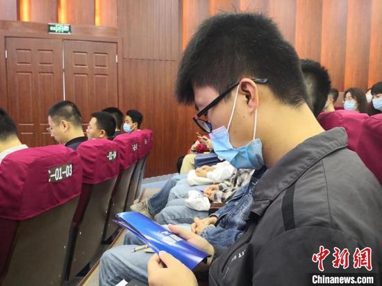 图为参加启动仪式学生学习网络安全知识宣传手册。 杜萍 摄