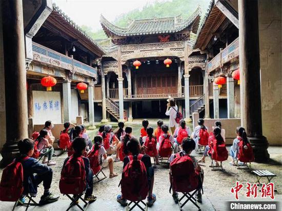 图为孩子们在一处历史建筑前接受革命传统文化教育。李明明摄