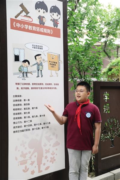 2021年5月26日,北京十八中附小法治展板前,学生法治宣讲团成员进行有关《中小学教育惩戒规则》的宣讲。