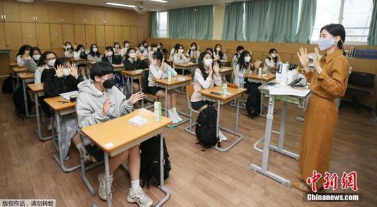图为韩国济州老师在课堂上带着口罩与学生们相互问候。