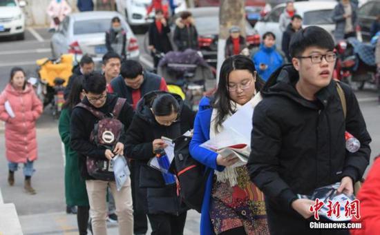 资料图:2018年12月22日,山东济南考点,考研学子排队进考场。 中新社记者 张勇 摄