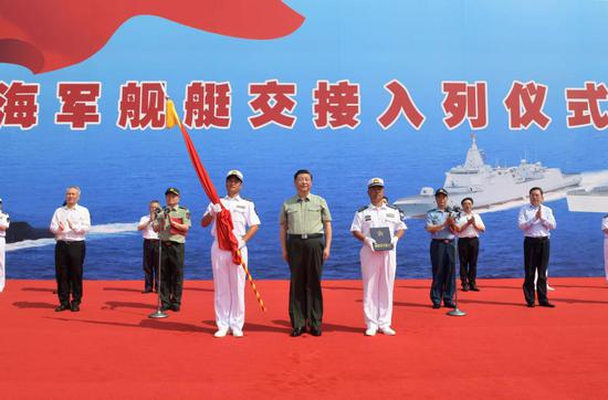 Chinese President Xi Jinping, also general secretary of the Communist Party of China Central Committee and chairman of the Central Military Commission, presents People's Liberation Army (PLA) flag and the naming certificate to the captain and political commissar of the Dalian in Sanya, south China's Hainan Province, April 23, 2021. Xi attended the commissioning ceremony of three naval vessels, the Changzheng-18, the Dalian, and the Hainan, and boarded the vessels after the ceremony. The vessels were delivered to the PLA Navy and placed in active service on Friday at a naval port in Sanya, south China's Hainan Province. (Xinhua/Li Gang)