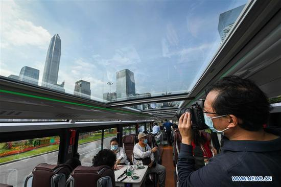 A journalist takes photos in a sightseeing bus in Shenzhen, south China's Guangdong Province, Oct. 22, 2020. Shenzhen on Thursday launched three sightseeing bus lines for tourists, which respectively showcase the culture, technology and night view of the city. (Xinhua/Mao Siqian)