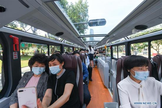 People take a sightseeing bus in Shenzhen, south China's Guangdong Province, Oct. 22, 2020. Shenzhen on Thursday launched three sightseeing bus lines for tourists, which respectively showcase the culture, technology and night view of the city. (Xinhua/Mao Siqian)