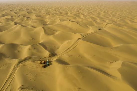 Aerial photo shows workers of the geophysical survey team carrying out drilling work in the Taklimakan Desert, northwest China's Xinjiang Uygur Autonomous Region, Feb. 24, 2021. (Xinhua/Hu Huhu)