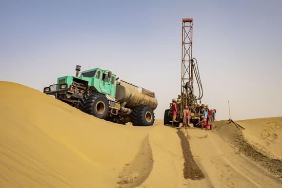 Workers of the geophysical survey team carry out the drilling work in the Taklimakan Desert, northwest China's Xinjiang Uygur Autonomous Region, Feb. 25, 2021. (Xinhua/Hu Huhu)