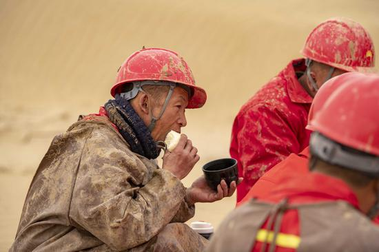 Workers of the geophysical survey team have lunch in the Taklimakan Desert, northwest China's Xinjiang Uygur Autonomous Region, Feb. 25, 2021. (Xinhua/Hu Huhu)