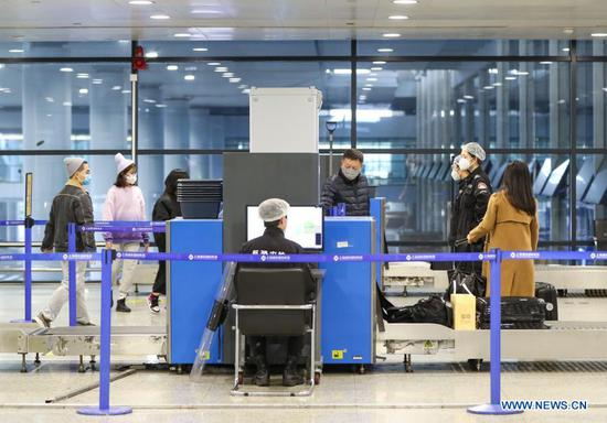 Passengers pass security checkpoint at Terminal 2 building of the Shanghai Pudong International Airport in east China's Shanghai, Nov. 24, 2020. The airport's recent daily throughput maintains at around 1,000 flights, with passengers wearing face masks and orderly moving in and out. (Xinhua/Ding Ting)