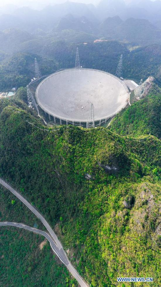 Aerial photo taken on March 28, 2021 shows China's Five-hundred-meter Aperture Spherical radio Telescope (FAST) under maintenance in southwest China's Guizhou Province. FAST has identified over 300 pulsars so far. Located in a naturally deep and round karst depression in southwest China's Guizhou Province, it officially began operating on Jan. 11, 2020. (Xinhua/Ou Dongqu)