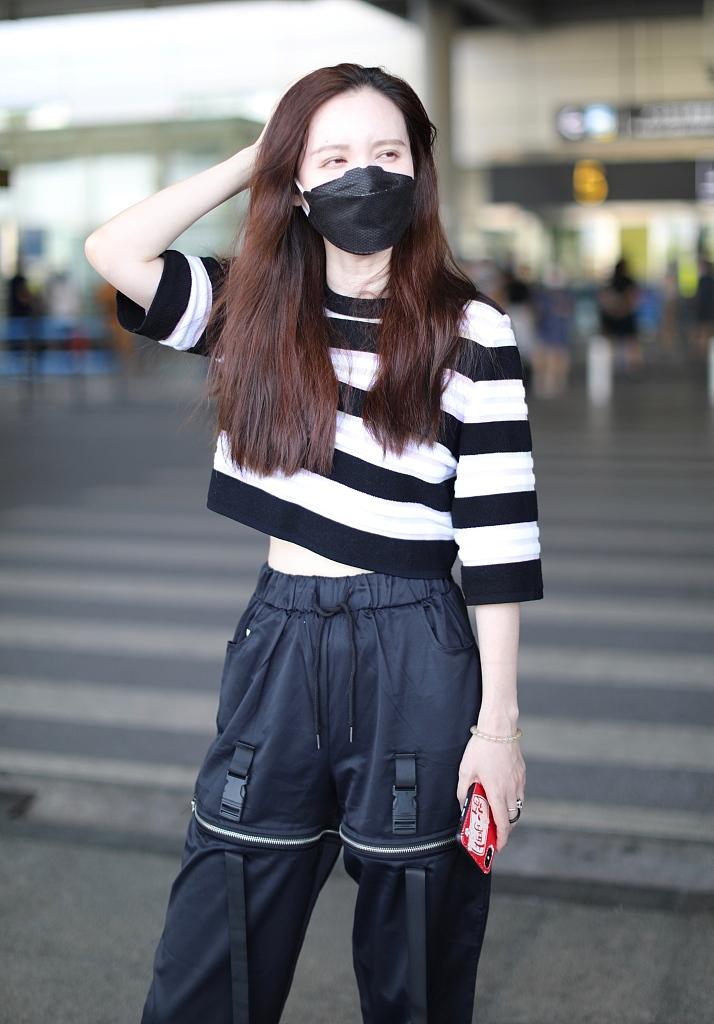 組圖:浪姐張萌長發披肩機場秀蠻腰 條紋衫工裝褲皮膚白到發光