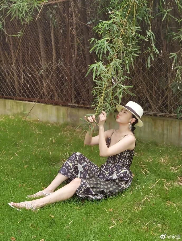 组图:宋佳草帽配吊带裙显风情 躺草地上悠闲伸展身姿优美
