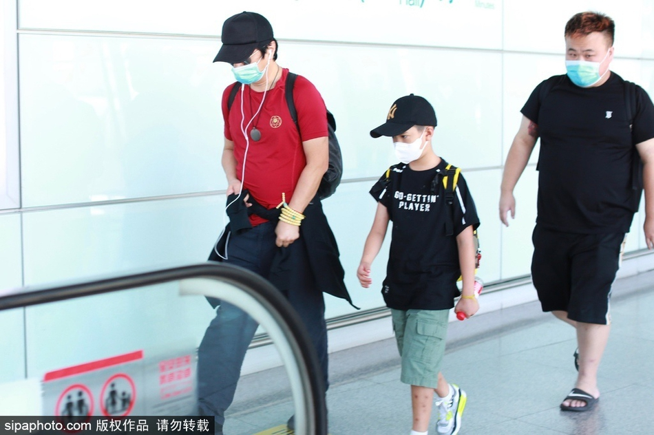 组图:郑钧穿红T恤现身机场休闲潇洒 一路牵儿子前行动作神同步