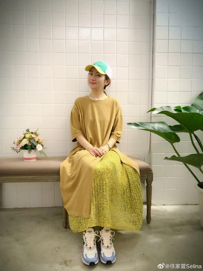 Selina穿长裙搭明黄鸭舌帽清新亮眼 捧花微笑甜美可人