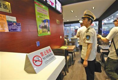2015年6月,工作人员在北京西站一咖啡厅内检查禁烟标识 新京报记者 王贵彬 摄