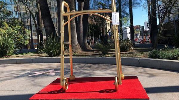 """街头艺术家塑料耶稣以韦恩斯坦的助步器为灵感的装置艺术作品""""最佳配角""""。"""