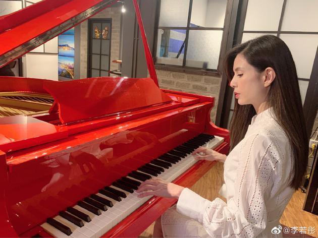 李若彤摆出弹钢琴的动作