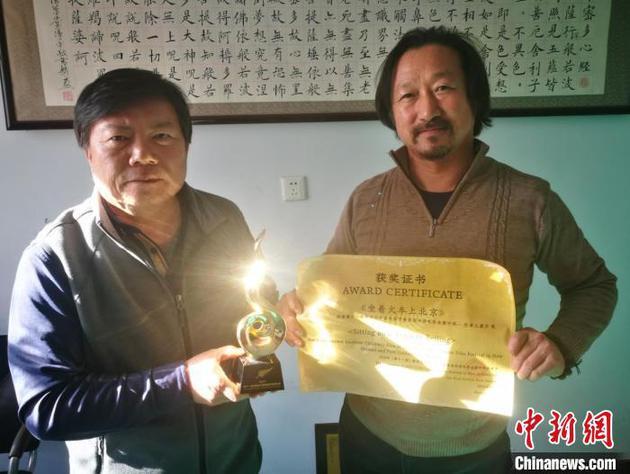 图为伊·呼和(左)与杨根和展示获奖证书。 李爱平 摄